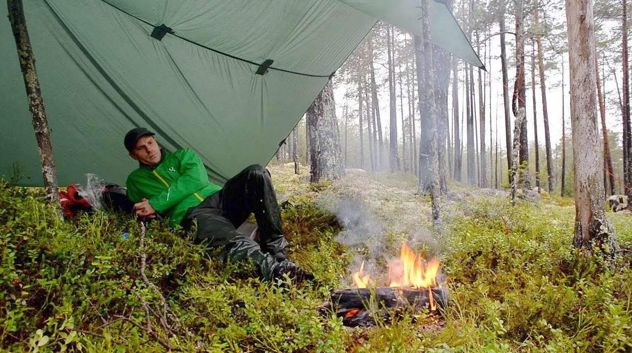 camp with tarp and fire in rain