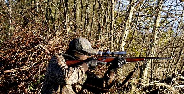 A hunter holding a rifle and aiming at its target